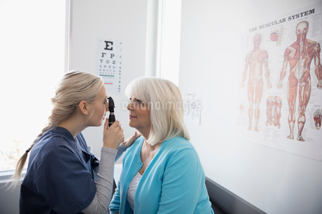 Female nurse examining eyes of senior patient with otoscope in clinic examination roomの写真素材 [FYI02313701]