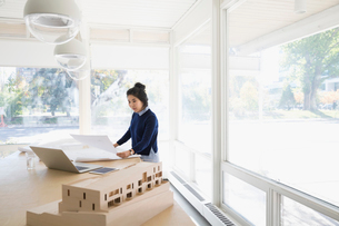 Female architect reviewing blueprints at table in officeの写真素材 [FYI02313719]