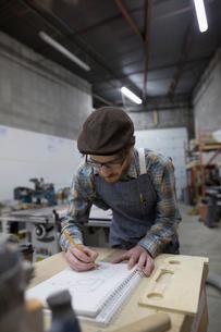 Male carpenter designing furniture in workshopの写真素材 [FYI02313753]