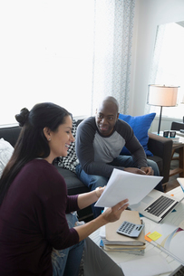 Couple at laptop discussing paperwork paying bills online in living roomの写真素材 [FYI02313864]