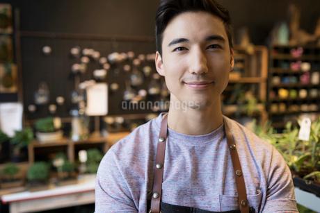 Close up portrait confident male shop owner in plant shopの写真素材 [FYI02313931]