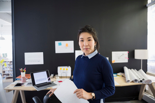 Portrait confident female architect with paperwork in officeの写真素材 [FYI02313949]