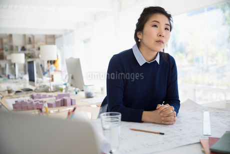 Pensive female architect looking away at blueprintsの写真素材 [FYI02313967]