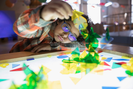 Curious boy playing with shapes at lighted display in science centerの写真素材 [FYI02313983]