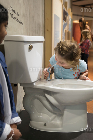 Girls drinking from toilet water fountain in science centerの写真素材 [FYI02314034]