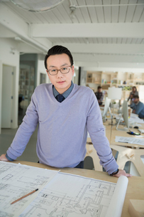 Portrait confident male architect working at blueprint in officeの写真素材 [FYI02314039]