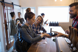 Female friends paying bartender for beers with smart phone contactless payment in brewery tasting roの写真素材 [FYI02314042]