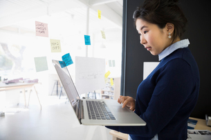 Businesswoman with laptop and adhesive notes at office glassの写真素材 [FYI02314048]