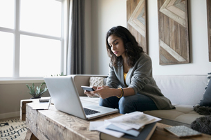 Young woman with laptop and calculator paying bills online on living room sofaの写真素材 [FYI02314054]