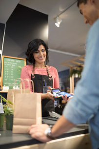 Female shop owner helping male customer paying with smart phone contactless payment at plant shop coの写真素材 [FYI02314081]