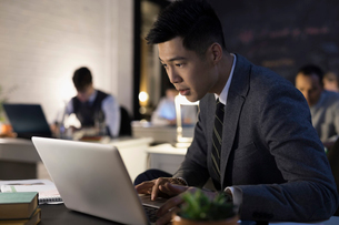 Focused businessman working at laptop in officeの写真素材 [FYI02314104]