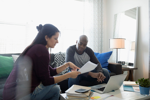 Couple at laptop discussing paperwork paying bills online in living roomの写真素材 [FYI02314110]