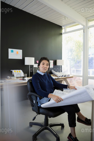 Portrait confident female architect reviewing blueprints in officeの写真素材 [FYI02314122]