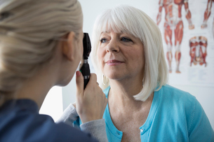 Female nurse examining eyes of senior patient with otoscope in clinic examination roomの写真素材 [FYI02314128]
