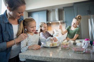 Mother and daughters baking in kitchen decorating cupcakesの写真素材 [FYI02314156]