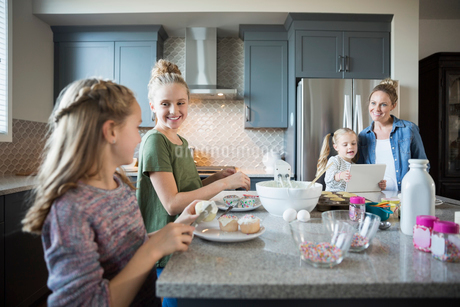 Mother and daughters baking in kitchen frosting cupcakesの写真素材 [FYI02314193]