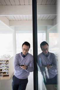 Male architect texting with cell phone in officeの写真素材 [FYI02314225]