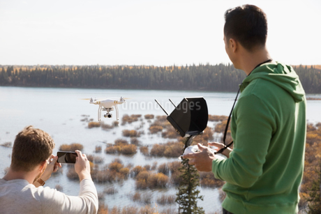 Male friends with drone equipment and camera phone overlooking lakeの写真素材 [FYI02314238]