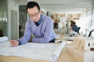 Focused male architect reviewing blueprint in officeの写真素材 [FYI02314263]
