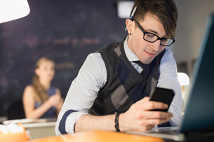 Businessman texting with cell phone at desk in officeの写真素材 [FYI02314309]