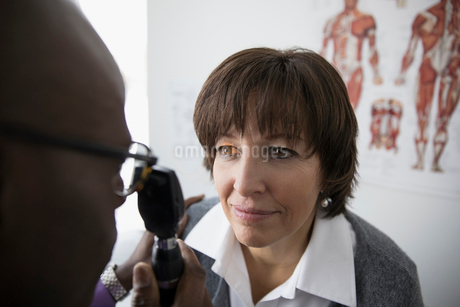 Male doctor examining eyes of female patient with otoscope in clinic examination roomの写真素材 [FYI02314367]