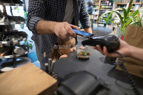 Close up father and daughter paying with smart phone contactless payment at plant shop counterの写真素材 [FYI02314373]