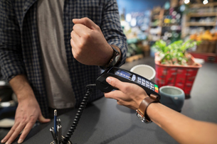 Close up male shopper paying with smart watch contactless payment at plant shopの写真素材 [FYI02314406]