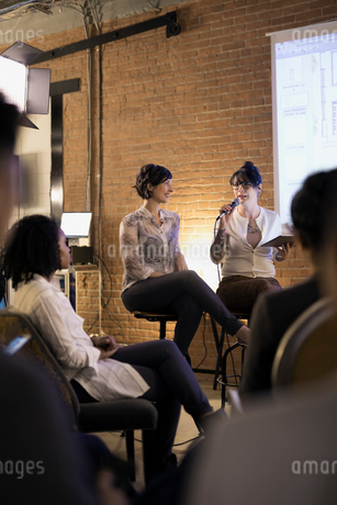 Female designers with microphone and digital tablet leading conference meetingの写真素材 [FYI02314419]