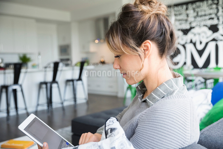 Woman using digital tablet on living room sofaの写真素材 [FYI02314449]