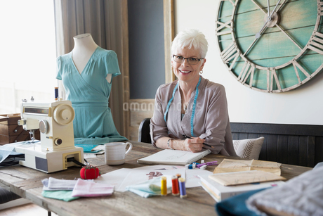 Portrait smiling senior woman seamstress working in home officeの写真素材 [FYI02314485]