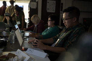 Focused hacker working hackathon at laptop in dark officeの写真素材 [FYI02314579]