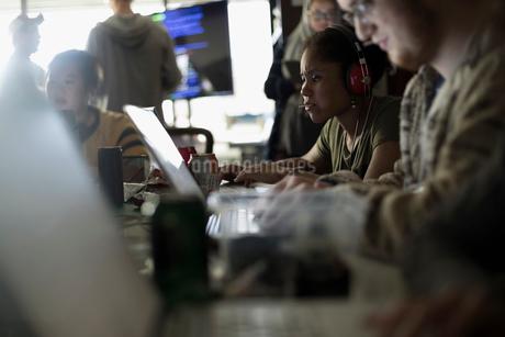 Focused hackers working hackathon at laptops in dark officeの写真素材 [FYI02314582]