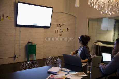Designers meeting viewing television monitor in conference roomの写真素材 [FYI02314630]