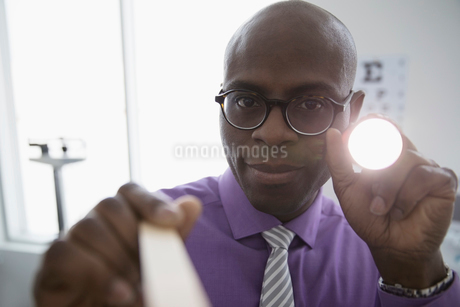 Personal perspective portrait male doctor using tongue depressor and flashlight in clinic examinatioの写真素材 [FYI02314656]