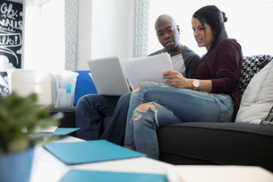 Couple with laptop discussing financial paperwork in living roomの写真素材 [FYI02314859]