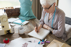 Senior woman seamstress sketching in notebook in home officeの写真素材 [FYI02314896]