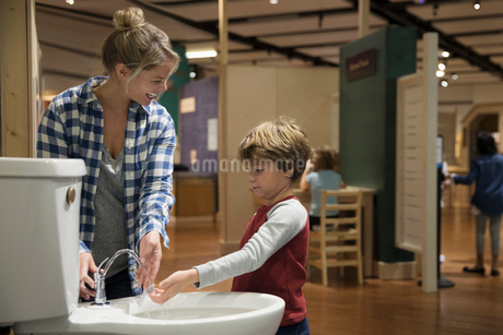 Mother and son drinking from toilet water fountain in science centerの写真素材 [FYI02314953]