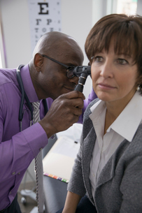 Male doctor examining ear of female patient with otoscope in medical examination roomの写真素材 [FYI02315080]