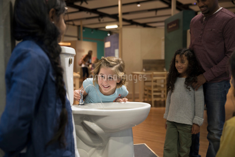 Girls drinking from toilet water fountain in science centerの写真素材 [FYI02315085]