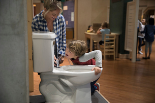 Mother and son drinking from toilet water fountain in science centerの写真素材 [FYI02315136]