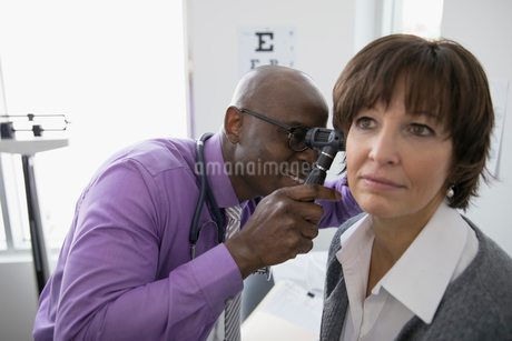 Male doctor examining ear of female patient with otoscope in medical examination roomの写真素材 [FYI02315395]