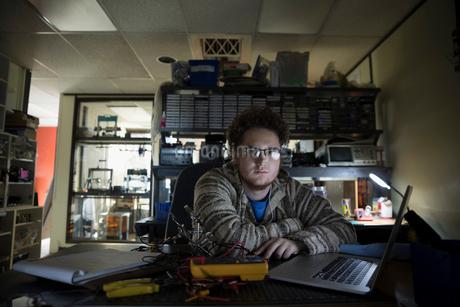 Portrait serious computer programmer working at laptop in dark officeの写真素材 [FYI02315398]