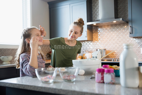 Playful sisters baking cupcakes in kitchen putting frosting on noseの写真素材 [FYI02315467]