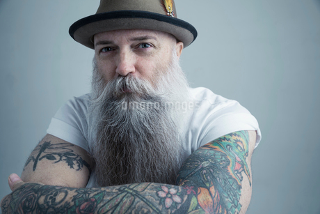 Portrait Caucasian male hipster with long gray beard and arm tattoos wearing fedoraの写真素材 [FYI02315538]