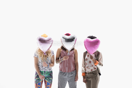 Women friends covering faces with heart-shape balloons against white backgroundの写真素材 [FYI02315618]
