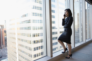 Businesswoman talking on cell phone at urban, highrise office windowの写真素材 [FYI02315624]