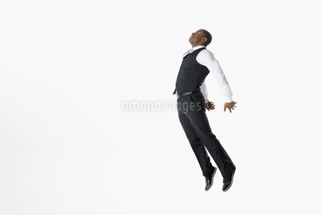 Businessman jumping chest forward against white backgroundの写真素材 [FYI02315654]