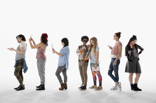 Cool young women using cell phones, standing in a row against white backgroundの写真素材 [FYI02315804]