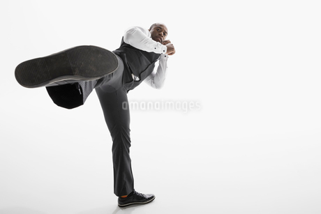 Portrait tough businessman kicking in fighting stance against white backgroundの写真素材 [FYI02315816]