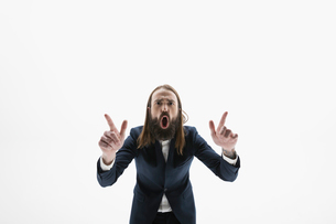 Portrait exuberant businessman with beard gesturing and yelling against white backgroundの写真素材 [FYI02315846]